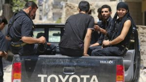 Rebels operating under the Free Syrian Army sit in a Hilux pickup truck on one of the battlefronts in Jobar, Damascus, August 2013